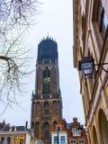 Der Turm der Dom-Kathedrale über einer Reihe von historischen Häusern von Utrecht, Holland lizenzfreie stockfotografie