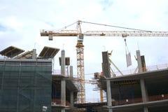 Der Turm, der Kran hochzieht, erhöhen Platten am Bauprozess auf konstruiertes Gebäude Lizenzfreies Stockbild