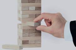 Der Turm von den Holzklötzen und Mann ` s von Hand nehmen einen Block Stockfotos