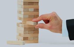 Der Turm von den Holzklötzen und Mann ` s von Hand nehmen einen Block Lizenzfreie Stockfotos