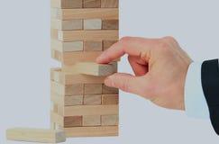 Der Turm von den Holzklötzen und Mann ` s von Hand nehmen einen Block Stockbilder