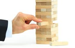 Der Turm von den Holzklötzen und von der Hand des Mannes Lizenzfreie Stockfotos
