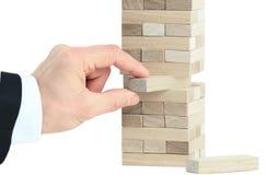Der Turm von den Holzklötzen und von der Hand des Mannes nehmen einen Block Lizenzfreie Stockfotos