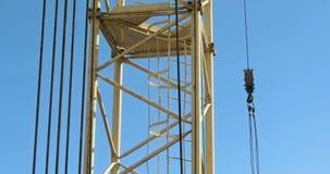Der Turmkran an der Baustelle gegen den blauen Himmel stock footage