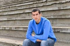 Der unglückliche Jugendstudent, der draußen auf Stadion sitzt, tritt Stockfotos