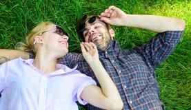 Der unrasierte Mann und das Mädchen legen auf Graswiese Paare in der Liebe vereinigt mit Natur Natur füllt sie mit Frische und lizenzfreies stockbild