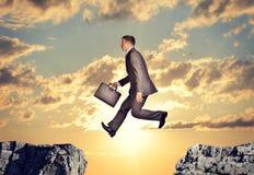 Der Unternehmer springend über Abgrund Lizenzfreies Stockbild