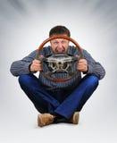 Der unwirkliche Geck mit einem Rad in den Händen Stockbild