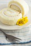 Der Vanillerollenkuchen und die gelbe Blume Stockfoto