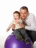 Der Vater, der mit kleinem Sohn auf der großen Kugel spielt Stockfotos