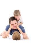 Der Vater, der mit Söhnen spielt Stockfotos