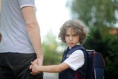 Der Vater führt durch die Hand in der Schule des kleinen Schülers Lizenzfreies Stockbild