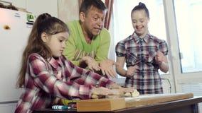 Der Vater der Familie unterrichtet seine Töchter, mit Down-Syndrom, Küchengeheimnisse stock footage