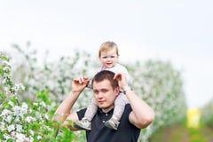 Der Vater hält die kleine Tochter auf einem Hals Stockfotos