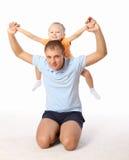 Der Vater hält die kleine Tochter in seinen Armen an Stockbild