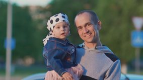 Der Vater hält eine kleine Tochter in seinen Armen und spricht mit ihr nave Sommer E stock video