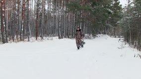 Der Vater nimmt das Kind auf einem Schlitten durch das Holz stock video