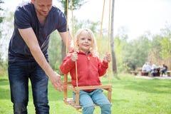 Der Vater, der seinen kleinen Sohn des blonden Haares auf dem Schwingen drückt Lizenzfreie Stockfotos