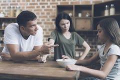 Der Vater spricht mit seiner traurigen Tochter, die am Tisch sitzt und nicht sein Frühstück essen möchte stockbild