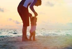 Der Vater und kleine Tochter, die auf Sonnenuntergang gehen, setzen auf den Strand Stockbild