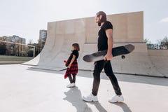 Der Vater und sein kleiner Sohn, die in der stilvollen zufälligen Kleidung gekleidet werden, gehen mit den Skateboards in ihren H stockbild