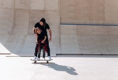 Der Vater und sein kleiner Sohn, die in der zufälligen Kleidung gekleidet werden, stehen zusammen auf dem einem Skateboard in ein lizenzfreies stockbild