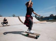 Der Vater und sein kleiner Sohn, die in der zuf?lligen Kleidung gekleidet werden, reiten Skateboards und haben Spa? in einem Roch stockbilder