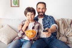 Der Vater und wenig Sohn zu Hause, die auf dem Sofajungen isst den Chip fernsieht sitzt, konzentrierten die zugeschalteten frohen stockbilder