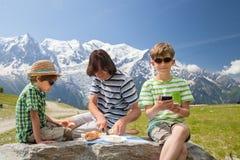 Der Vater und zwei Jungen haben Picknick in den Bergen Lizenzfreie Stockfotografie