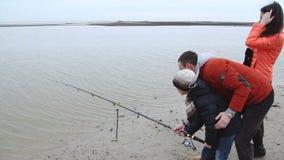 Der Vater unterrichtet seinen Sohn, den Köder zu werfen Autumn Fishing Rods stock video footage