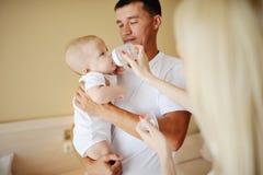Der Vati, der ein Baby in ihren Armen hält, Mutter zieht ihre Babysohnflasche ein stockfotografie