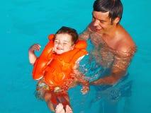 Der Vati erlernt, das Kind zu schwimmen Stockfoto