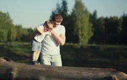 Der Vati und Sohn gehen, Vater hilft Kind, Babyschritte zu machen Stockfoto