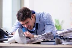 Der verärgerte Geschäftsmann frustriert mit zu vieler Arbeit stockfotografie