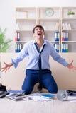 Der verärgerte Geschäftsmann frustriert mit zu vieler Arbeit stockfoto