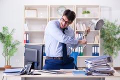 Der verärgerte Geschäftsmann frustriert mit zu vieler Arbeit stockbild
