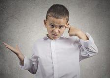 Der verärgerte Junge, der mit dem Finger gegen Tempel gestikuliert, sind Sie verrückt? lizenzfreie stockfotografie