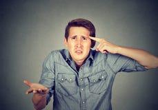 Der verärgerte Mann, der mit seinem Finger gegen Tempel gestikuliert, sind Sie verrückt? Stockbilder