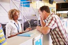 Der verärgerte Passagier, der zum Personal am Flughafen sich beschwert, überprüfen herein lizenzfreies stockfoto