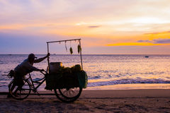 Der Verkäufer auf dem Strand in Vietnam bei Sonnenuntergang Ein Mann trägt einen Warenkorb des Lebensmittels stockbild