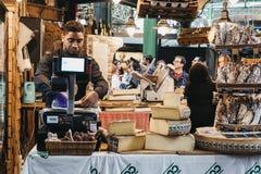 Der Verkäufer, der Käse am Feinkostgeschäft wiegt und einwickelt, stehen am Stadt-Markt, London stockfotografie