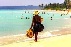 Der Verkäufer von Hüten geht entlang das mit gelbem Sand des Strandes entlang lizenzfreie stockbilder