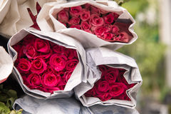 Der Verkauf blüht - einen Blumenstrauß von den Roten/Rosarosen, die im Papier eingewickelt werden Lizenzfreie Stockbilder