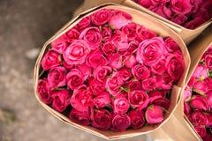 Der Verkauf blüht - einen Blumenstrauß von den Roten/Rosarosen, die im Papier eingewickelt werden Stockbild