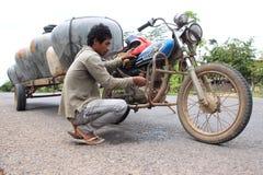 Der Verkauf des Wassers barrels von einem Motorrad in Kambodscha stockfotos