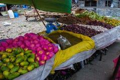 Der Verkauf trägt an einem Markt in den Philippinen Früchte Verkaufs-Mango, Äpfel, Knoblauch, Samen Stockfotografie