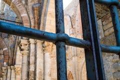 Der verrostete Eisenzaun von Kathedrale Sans Galgano, in Toskana stockfotografie