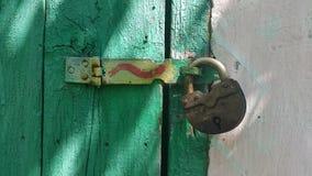 der Verschluss auf dem alten Türgrün Stockfotos