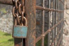 Der Verschluss auf der Kette Alte rostige Kette mit einem Verschluss auf dem Eisentor Symbolgefangenschaft und -sklaverei Stockfoto