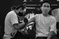 Der vietnamesische Mann, der ein weißes T-Shirt trägt, erhält eine Tätowierung auf seinem rechten Arm durch Recycle Tätowierungs- stockbilder